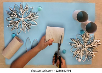 Christmas crafted snowflakes with paper toilette roll lays on the blue color background, original craft and diy concept for kid and kindergarten, flat lay, step by step
