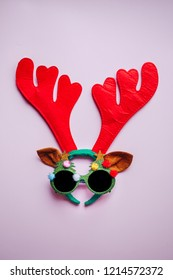 christmas creative concept background. flat lay top view of reindeer antlers and xmas party glasses. perfect for a merry xmas greeting card or party invite. enough room for copy space.