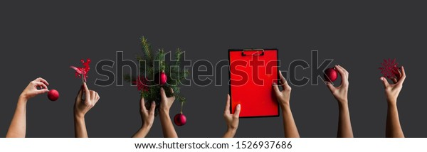Christmas creative flat lay. Woman's hands are raised up and holding a variety of Christmas decorations, balls, fir branches, red, Christmas card banner on a dark background