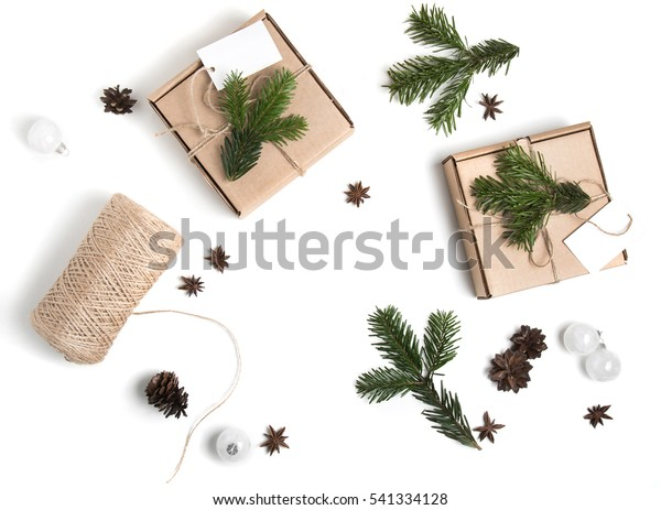 Christmas creative process composition. Presents with empty tag and decor of fir-tree branches, rope, craft paper and pine cones. Holiday composition on white background. Top view flat lay