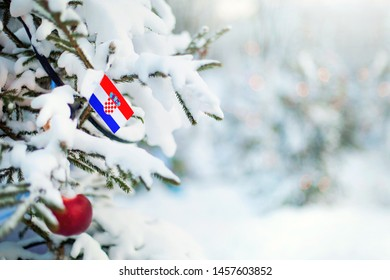 Christmas Croatia. Xmas tree covered with snow, decorations and a flag of Croatia. Snowy forest background in winter. Christmas greeting card.