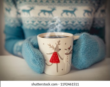 Christmas cup of coffee in female hands.