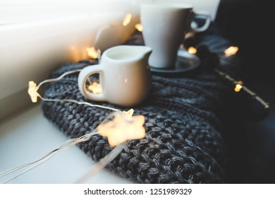 Christmas cup of coffee on window with christmas star garland and milk over knitted plaid.  Warm festive winter backdrop. Cozy hugge atmosphere with cup of coffee with milk close up, for greeting card