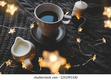 Christmas cup of coffee top view with christmas star garland and milk over knitted plaid.  Warm festive winter backdrop. Cozy hugge atmosphere with cup of coffee with milk close up, for greeting card.