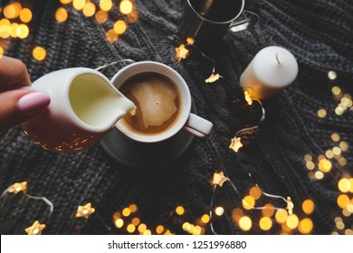 Christmas cup of coffee top view with christmas star garland and milk over knitted plaid.  Warm festive winter backdrop. Cozy hugge atmosphere with woman hand holding milk, for greeting cards.