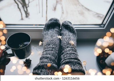 Christmas cup of tea on window with christmas star garland, bokeh and woman legs, knitted socks.  Warm festive winter backdrop. Cozy hugge atmosphere with cup of tea, xmas decor, for greeting card
