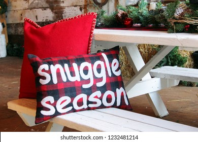 Christmas cushion that says snuggle season on a wooden rustic table.