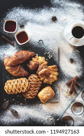 Christmas dark background with cup of coffee and croissants and bakery. New Year mood. Top view with special copyspace for text and design.