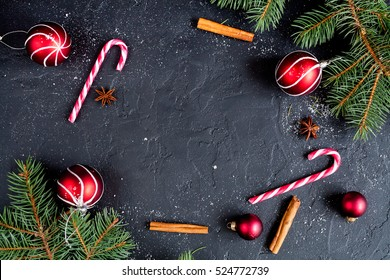 Christmas dark background with christmas decoration, christmas candy canes, fir branch, top view