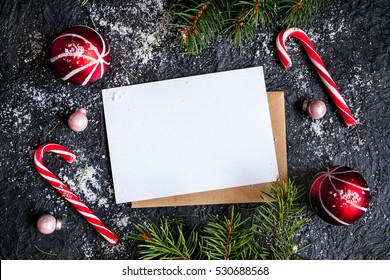 Christmas dark background with christmas decoration, christmas candy canes, christmas balls and fir branch, top view
