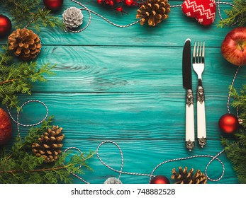 Christmas dark green frame background with pine cones, red baubles and twine. Fork and knife on wooden table texture. Festive holiday dinner