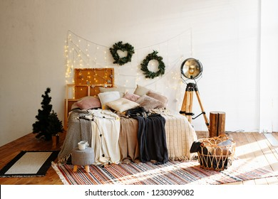 Christmas decor. Bedroom in bright colors with large Windows and a huge bed. The interior is decorated with garlands, Christmas wreaths and a small Christmas tree.Modern style.