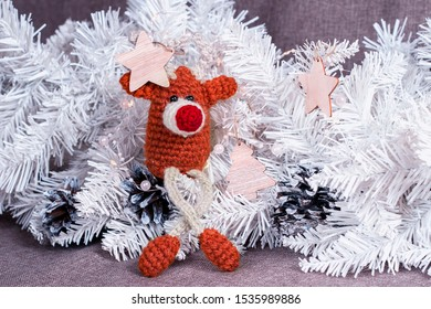 Christmas decor of crochet deer toy and christmas tree with cones