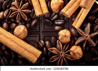 Christmas decor with dark chocolate coffee beans cinnamon nuts and star anise and empty place for text