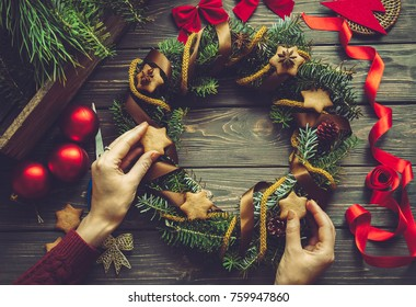 Christmas decor. Females hands decorating a wreath with natural decoration. Winter Holidays tradition concept