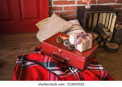 Christmas decor. Festively decorated Christmas interior in red and brown colors. Horizontal color image of photo booth with brick brown wall, wooden floor, painted door,  pillows, presents.