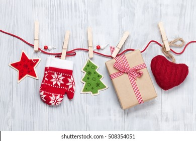 Christmas decor and gift box on rope over wooden background