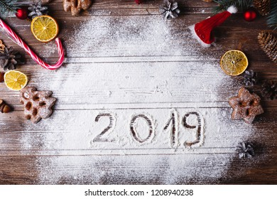 Christmas decor and place for text. White snow with number 2019 lies on a table surrounded with cookies, Christmas tree toys and other decor