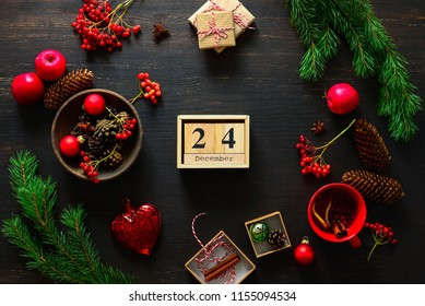 Christmas decor stuff on moody table top ready for setting a dinner table, cup of winter warmer standing below, cones, fruits and winter berries around the calendar