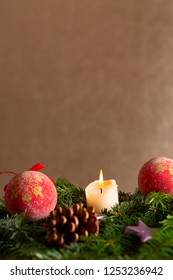 christmas decor with tree-balls, candle, branch and cone in front of golden background