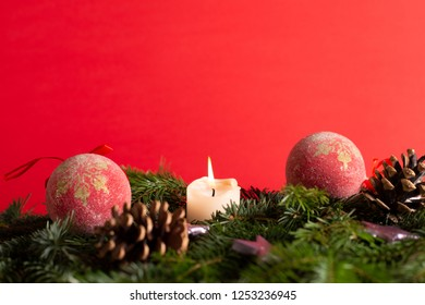christmas decor with tree-balls, candle, branch and cone in front of red background