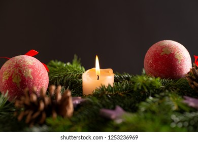 christmas decor with tree-balls, candle, branch and cone