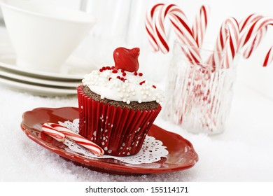 Christmas decorated chocolate cupcake with vanilla frosting and candy-canes.