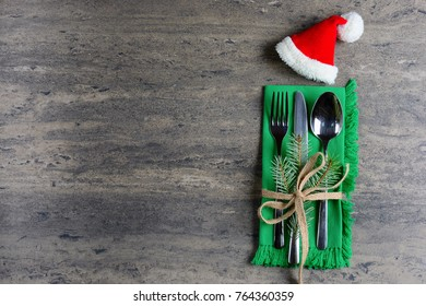 Christmas, decorated cutlery with a Santa hat on a green napkin, decorated with a sprig of pine and ribbon.  Christmas and New Year Holidays background, top view. Creative idea.