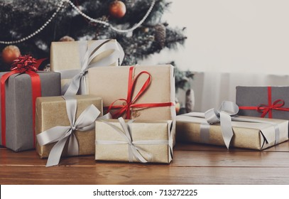 Christmas decorated gifts on table, closeup, selective focus. Christmas tree background.