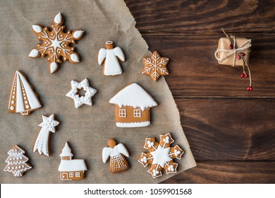 Christmas decorated gingerbread cookies on cooking paper over old brown wooden background. Decorated by festive decor. Christmas and celebration concept. Top view.