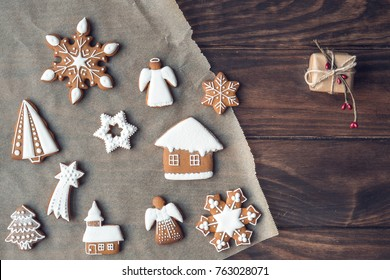 Christmas decorated gingerbread cookies on cooking paper over old brown wooden background. Decorated by festive decor. Christmas and celebration concept. Top view. Toned with old style sepia colors.