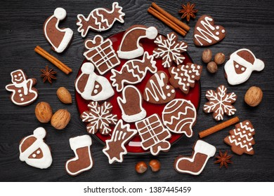 Christmas - decorated gingerbread with icing on a red plate and black wood and nuts and anise and cinnamon