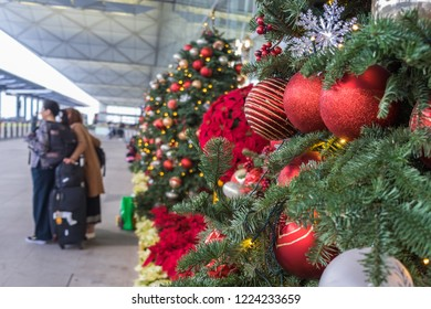 Christmas decoration in airport. Outside departure zone in Hong Kong International Airport. Christmas trees in line decorated with balls, snowflakes and garlands. Unrecognizable people on background.