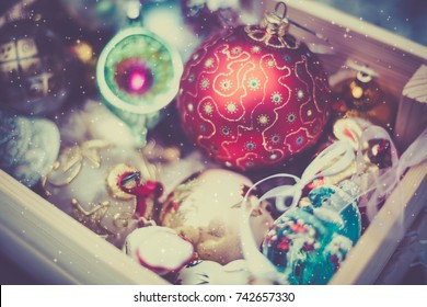 Christmas decoration balls in a wooden box outdoors on winter snow background