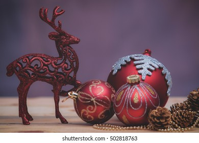 Christmas decoration with baubles christmas ornaments on wooden table over purple grunge background. retro style