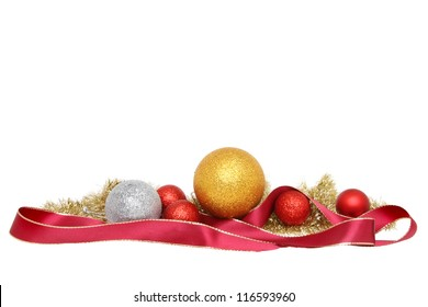 Christmas decoration of baubles tinsel and gold edged red ribbon isolated against white
