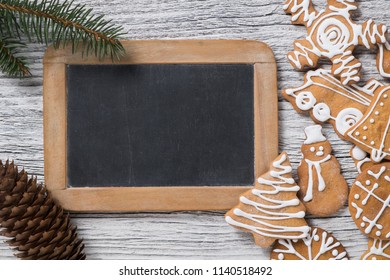 Christmas decoration. Blackboard with fir tree twig and gingerbread cookie. Empty space for text.