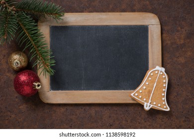 Christmas decoration. Blackboard and gingerbread Bell, spruce twig and Christmas tree balls. Empty space for text.