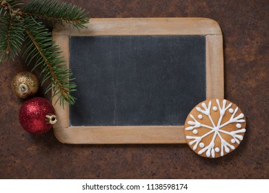 Christmas decoration. Blackboard and gingerbread Snowflake, spruce twig and Christmas tree balls. Empty space for text.