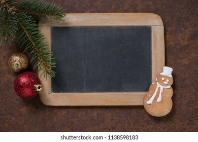 Christmas decoration. Blackboard and gingerbread Snowman, spruce twig and Christmas tree balls. Empty space for text.