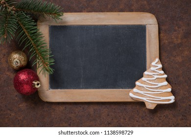 Christmas decoration. Blackboard and gingerbread Christmas tree, spruce twig and Christmas tree balls. Empty space for text.