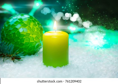 Christmas decoration with candle and ball in the snow