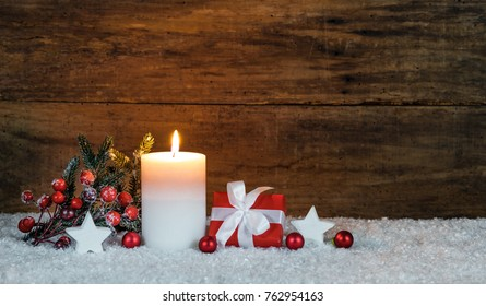 Christmas decoration with candle, gift box, ornaments and wooden background