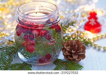 Christmas decoration. Candle in glass jar with cranberry and fir