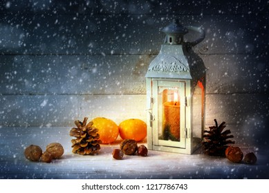 christmas decoration with a candle light lantern, tangerines, cones and nuts in the snow on rustic wood at night, copy space, selected focus