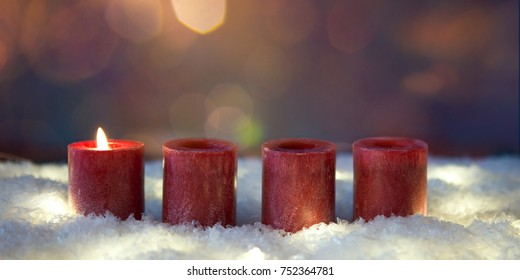 christmas decoration  candles in snow for advent season one candle burning