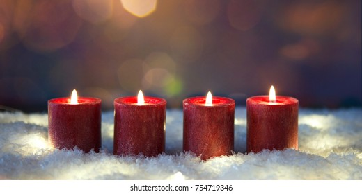 christmas decoration  candles in snow for advent season four candles burning
