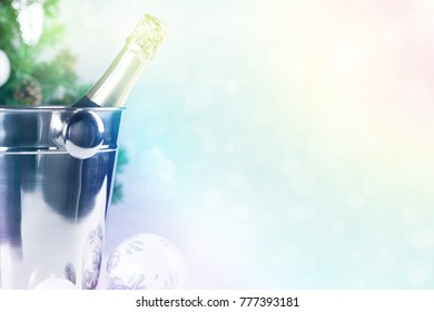 Christmas decoration card with champagne bottle in ice bucket on silver glittering background, defocused lights and fir tree, nobody