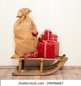 Christmas decoration in classical colors red and white with presents and an old sledge.