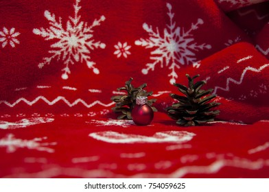 Christmas decoration from cones, christmas ball, candle and snow, on red christmas background with snow flakes.
